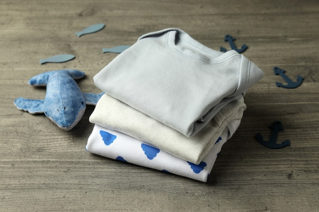Concept of cute baby clothes on gray textured background.