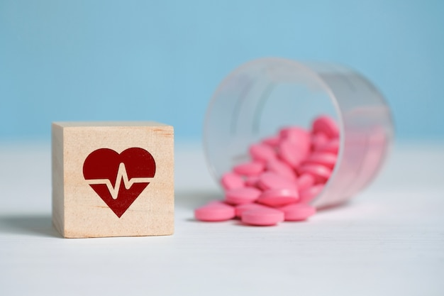 The concept of a daily dose of medication for the heart. icon on a wooden square next to tablets made of plastic cup.