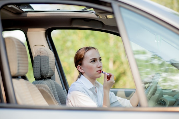 Concept of danger driving. young woman driver red haired teenage girl painting her lips doing applying make up while driving the car