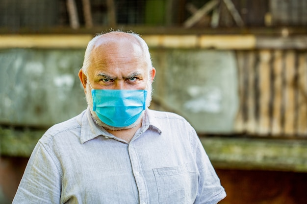 Понятие опасности коронавируса для пожилых людей. портрет старика в хирургической повязке, коронавирусе, медицинской маске.
