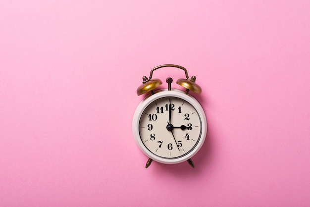 Concept of daylight saving time. retro clock on the pink background. top down view with copy space