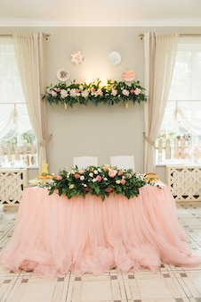 The concept of decor for weddings and holidays, floral arrangements on the tables, the presidium of the newlyweds