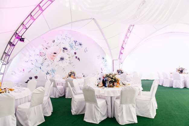 Concept of decoration for wedding and celebration, a beautiful white tent decorated with flowers for the holiday