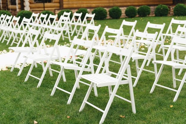Concept of decoration for wedding and party, white chairs for wedding guests ceremony