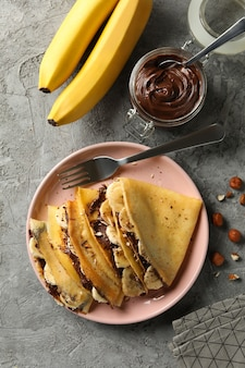Concept of delicious breakfast with crepes with chocolate paste, banana and nuts on gray background