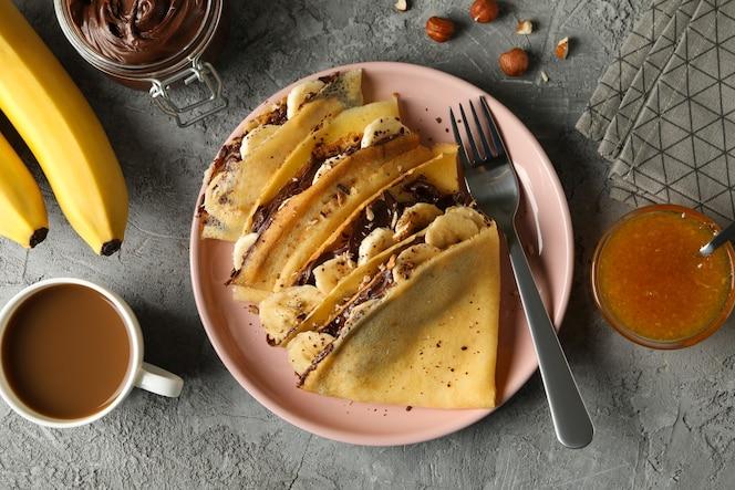 concetto di deliziosa colazione con crepes con pasta di cioccolato, banana e noci su sfondo grigio