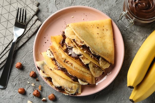 Concept of delicious breakfast with crepes with chocolate paste, banana and nuts on gray surface