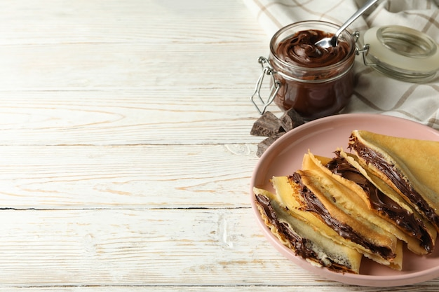 Concept of delicious breakfast with crepes with chocolate paste on white wooden background