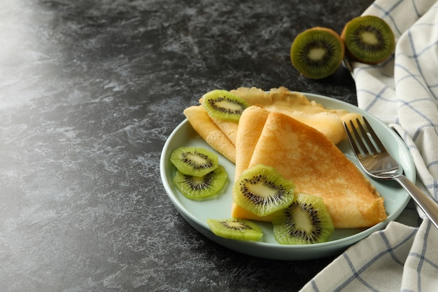 Concept of delicious breakfast with crepes with kiwi on black smokey surface