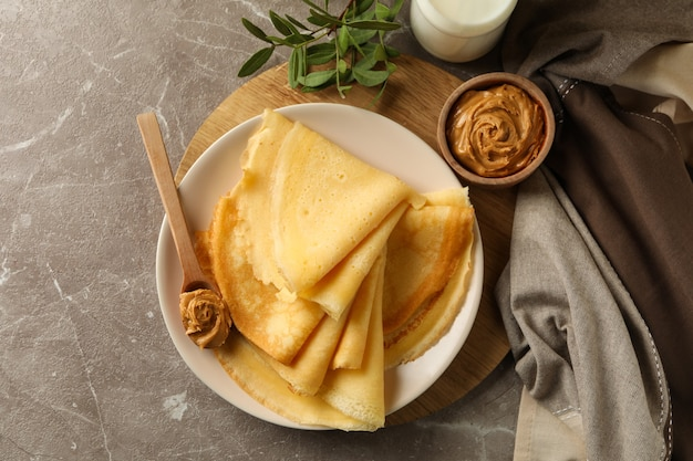 Concept of delicious breakfast with crepes with peanut butter and milk on gray table