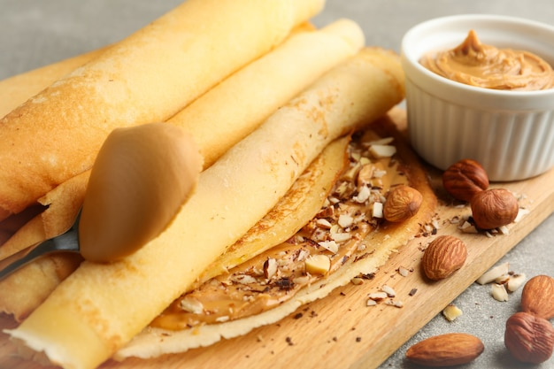 Concept of delicious breakfast with crepes with peanut butter and nuts on gray table
