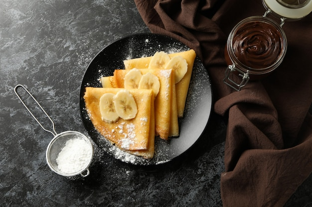 Concept of delicious breakfast with crepes with sugar powder and banana on black smokey background
