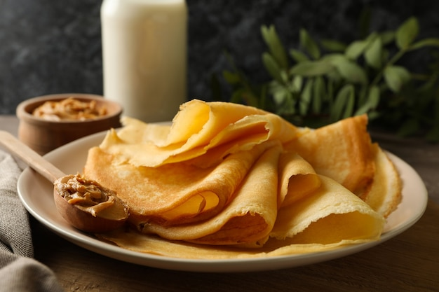 Concept of delicious breakfast with plate of crepes with peanut butter on wooden board
