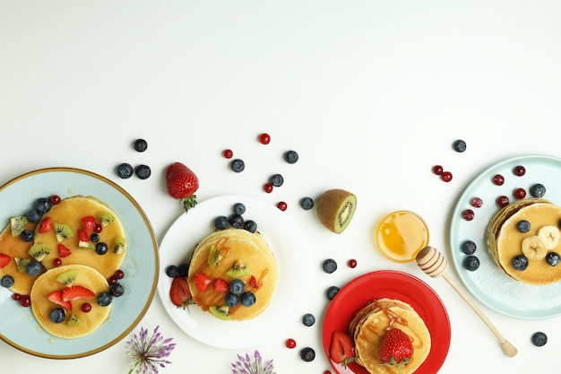 Concept of delicious dessert with pancakes on white background