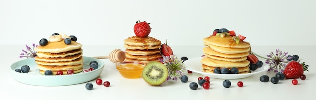 Concept of delicious dessert with pancakes on white table