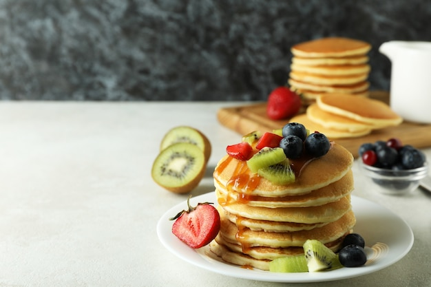 Concept of delicious dessert with pancakes on white textured table