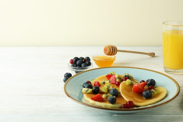Concept of delicious dessert with pancakes on white wooden table