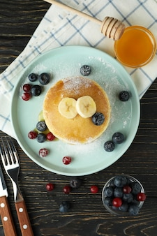 Concept of delicious dessert with pancakes on wooden table