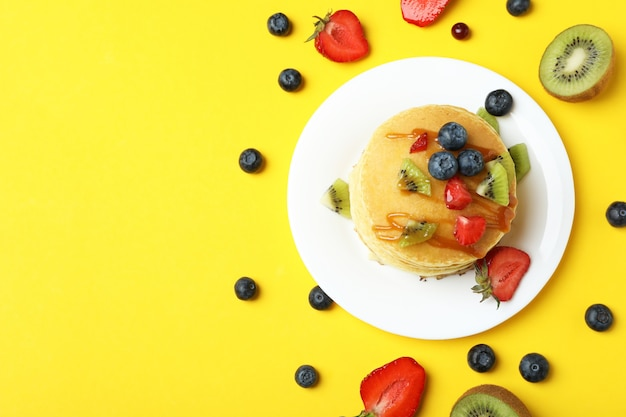 Concept of delicious dessert with pancakes on yellow background