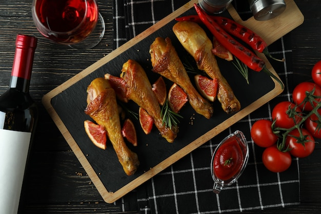 Concept of delicious eating with board of roast chicken drumsticks on wooden table