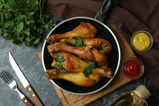 Concept of delicious eating with pan of roast chicken drumsticks on black smokey table