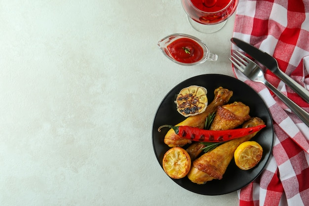 Concept of delicious eating with roast chicken drumsticks on white textured table