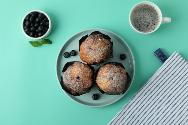 Concept of delicious food with chocolate muffins on mint background.