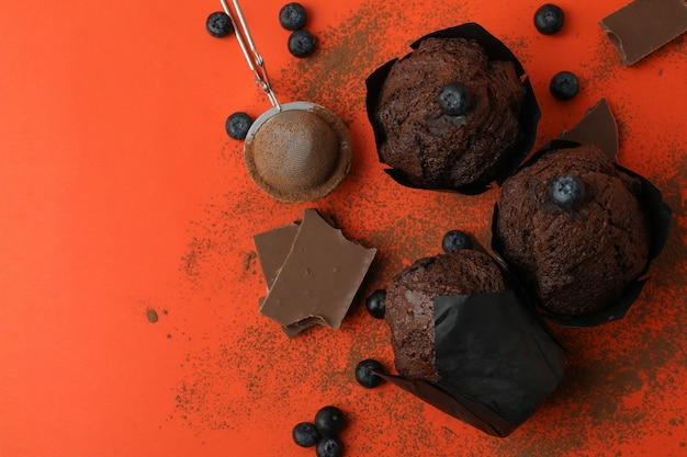 Concept of delicious food with chocolate muffins on orange background.