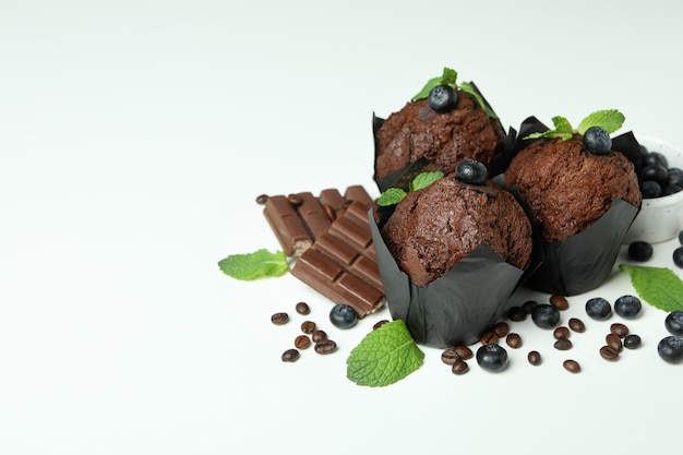 Concept of delicious food with chocolate muffins on white background.