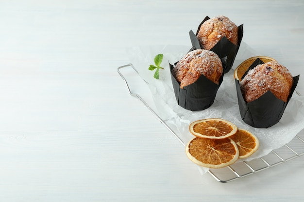 Concept of delicious food with chocolate muffins on white wooden table.