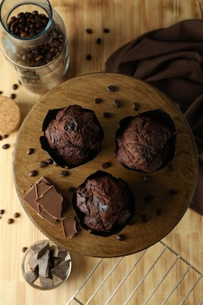 Concept of delicious food with chocolate muffins on wooden background.