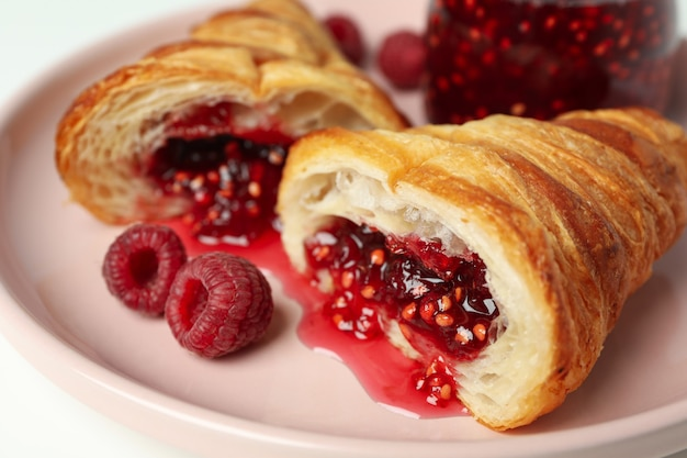 Concept of delicious food with croissant with raspberry jam on white background