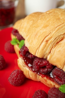 Concept of delicious food with croissant with raspberry jam on wooden background
