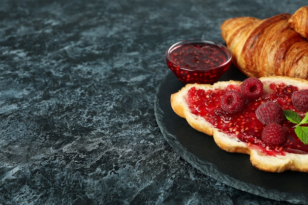 Concept of delicious food with croissants with raspberry jam on black smokey background