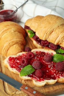 Concept of delicious food with croissants with raspberry jam, close up