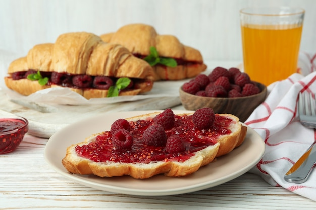 Concept of delicious food with croissants with raspberry jam on white wooden background