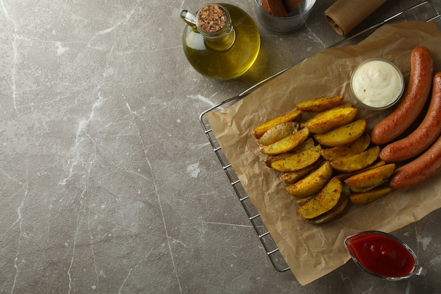 Concept of delicious meal with potato wedges, sauce and sausage