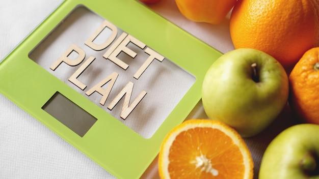 コンセプトダイエット。健康食品、キッチン体重計。野菜や果物のレタリングダイエット計画