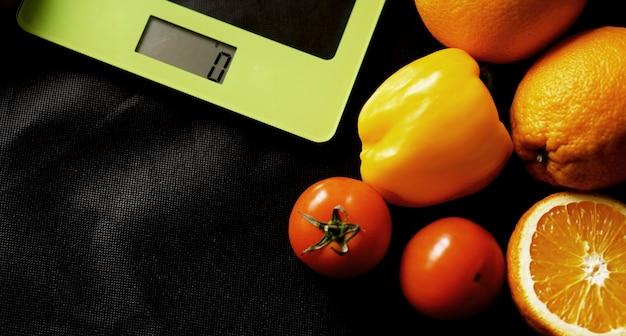 コンセプトダイエット。健康食品、キッチン体重計。野菜と果物。黒い表面の上面図のクローズアップ