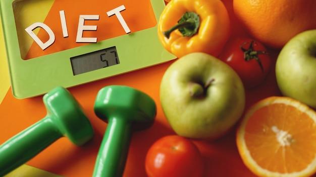 개념 다이어트. 건강에 좋은 음식, 주방 체중계. 야채와 과일. 오렌지 배경에 상위 뷰 클로즈업