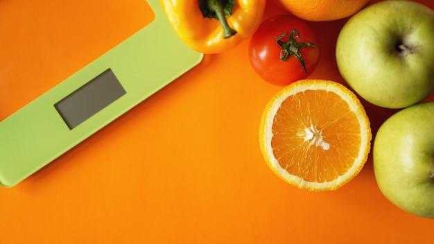 コンセプトダイエット。健康食品、キッチン体重計。野菜と果物。オレンジ色の表面の上面図のクローズアップ