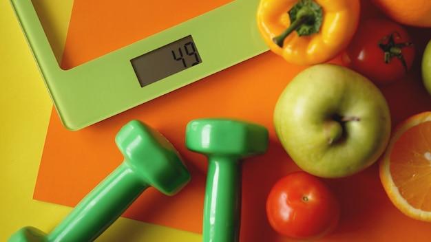 개념 다이어트. 건강 식품, 주방 체중계. 야채와 과일. 주황색 표면에 상위 뷰 클로즈업