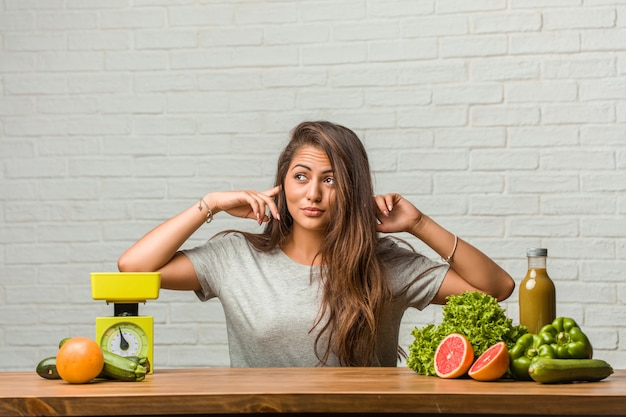 Concept of diet. portrait of a healthy young latin woman covering ears with hands, angry and tired of hearing some sound