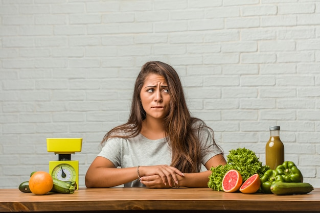 Concept of diet. portrait of a healthy young latin woman doubting and confused, thinking of an idea or worried about something