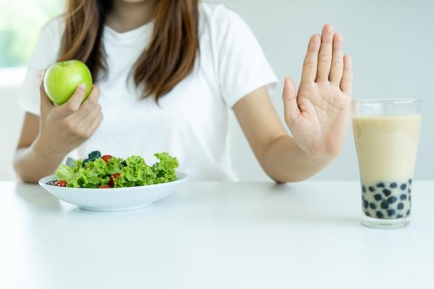 개념 다이어트와 건강. 건강한 여성은 진주 밀크티를 먹지 않고 사과와 샐러드 야채를 선택합니다. 여성은 지방과 전분이 포함 된 음식과 음료를 거부하지만 건강한 비타민 식품을 섭취합니다.