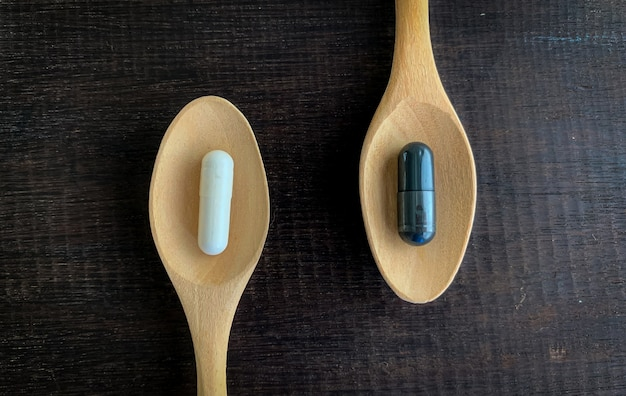 The concept of different choices,white pills and black pills are placed on a wooden spoon