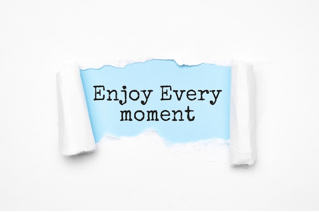 Concept of discovering enjoy every moment. uncovered unrolled beige torn paper and search engine optimization abbreviation.