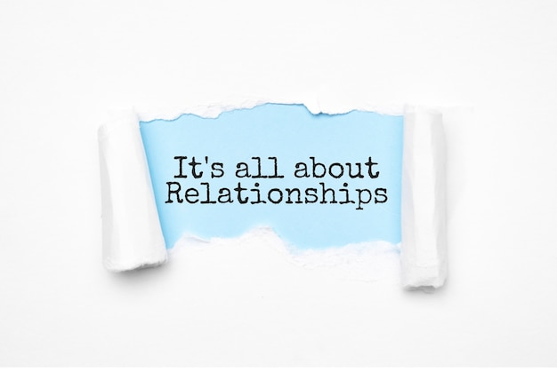 Concept of discovering it's all about relationships. uncovered unrolled beige torn paper and search engine optimization abbreviation.