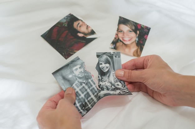 Concept of divorce, betrayal, separation, hand ripping photo of couple