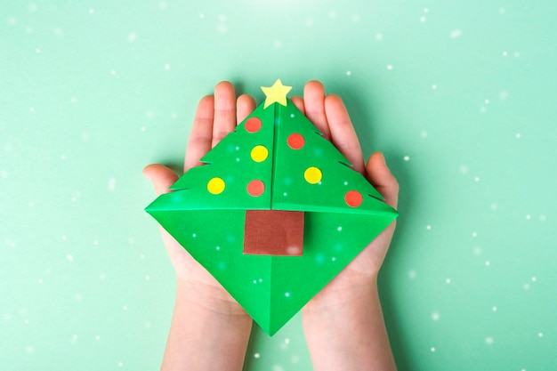 Concept of diy and kid's creativity, origami. child's hand holding bookmark as christmas tree.